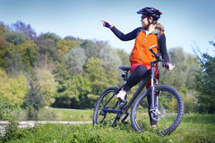 Ciclista femenino que señala en un lago Foto de archivo libre de regalías
