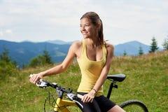 Ciclista femminile attraente con la bicicletta gialla della montagna, godente del giorno soleggiato nelle montagne immagine stock libera da diritti