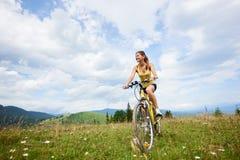 Ciclista femminile attraente con la bicicletta gialla della montagna, godente del giorno soleggiato nelle montagne fotografie stock libere da diritti