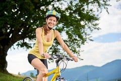 Ciclista femminile attraente con la bicicletta gialla della montagna, godente del giorno soleggiato nelle montagne immagini stock libere da diritti