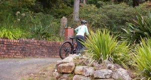 Ciclista femminile che cammina con il mountain bike in foresta alla campagna stock footage