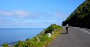 Ciclista femminile che cicla su una strada costiera un giorno soleggiato 4k video d archivio