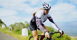 Ciclista femminile che cicla su una strada 4k della Costa video d archivio