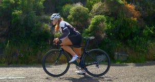 Ciclista femminile che inizia riciclaggio su una strada 4k della campagna stock footage