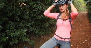 Ciclista femminile che prende una rottura mentre ciclando nella foresta archivi video