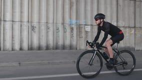 Ciclista focalizado apto seguro que monta um capacete vestindo da bicicleta, um equipamento preto e uns óculos de sol Bicicleta p vídeos de arquivo