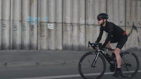 Ciclista focalizado apto seguro que monta um capacete vestindo da bicicleta, um equipamento preto e uns ?culos de sol Bicicleta p vídeos de arquivo
