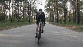 Ciclista forte que monta uma bicicleta fora da sela Ciclista com pedaling forte dos músculos do pé Siga para tr?s o tiro Conceito filme