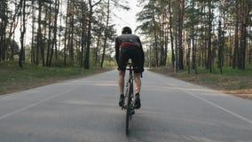 Ciclista forte que monta uma bicicleta fora da sela Ciclista com pedaling forte dos m?sculos do p? Siga para tr?s o tiro Conceito filme