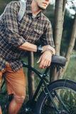 Ciclista irreconocible del hombre joven que se coloca con la bicicleta cerca de árbol en parque del verano y concepto de reclinac Foto de archivo libre de regalías