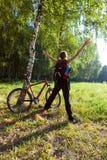 Ciclista joven emocionado que se coloca en un parque de la primavera Imagenes de archivo