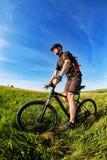 Ciclista joven en el casco en el prado verde en un fondo con el cielo azul Imágenes de archivo libres de regalías