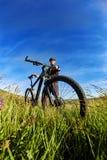 Ciclista joven en el casco en el prado verde en un fondo con el cielo azul Fotografía de archivo libre de regalías