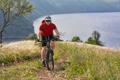Ciclista joven que completa un ciclo en el prado verde del verano contra paisaje hermoso Foto de archivo