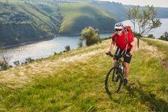 Ciclista joven que completa un ciclo en el prado verde del verano contra paisaje hermoso Foto de archivo libre de regalías