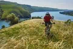Ciclista joven que completa un ciclo en el prado verde del verano contra paisaje hermoso Imagen de archivo