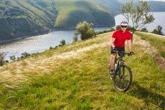 Ciclista joven que completa un ciclo en el prado verde del verano contra paisaje hermoso Fotos de archivo libres de regalías