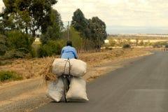 Ciclista keniano che prende a casa o che consegna alimentazione animale Fotografia Stock Libera da Diritti