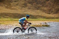 Ciclista a la velocidad del río móvil de la montaña Foto de archivo libre de regalías