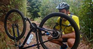 Ciclista maschio che ripara il pneumatico della bicicletta stock footage