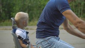 Ciclista maschio con il figlio, bambino nel sedile del bambino video d archivio