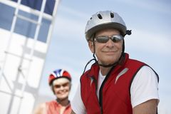 Ciclista maschio sorridente con la donna nei precedenti Fotografia Stock Libera da Diritti