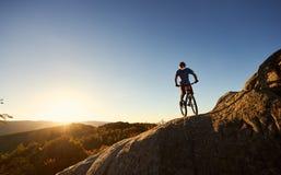 Ciclista maschio sulla bicicletta di prova sulla cima del masso all'aperto fotografia stock libera da diritti