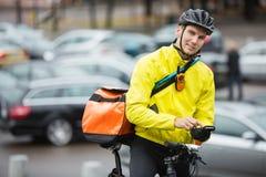 Ciclista masculino con el teléfono de Bag Using Mobile del mensajero Imagenes de archivo