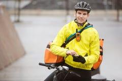Ciclista masculino con el teléfono de Bag Using Mobile del mensajero Fotografía de archivo libre de regalías