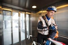 Ciclista masculino con el teléfono de Bag Using Mobile del mensajero Imágenes de archivo libres de regalías
