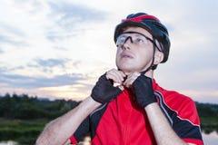 Ciclista masculino que fija su casco protector al aire libre en la hora de oro Fotografía de archivo libre de regalías