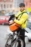 Ciclista masculino que pone el paquete en el mensajero Bag On Fotos de archivo libres de regalías