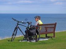 Ciclista mayor en banco costero Foto de archivo