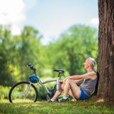 Ciclista mayor que se sienta por un árbol en parque Imágenes de archivo libres de regalías