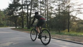 Ciclista messo a fuoco sicuro che pedaling sulla bicicletta nel parco Addestramento di riciclaggio della strada Concetto di ricic archivi video