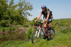 Ciclista in mountain-bike accanto ad un bello fiume Fotografia Stock Libera da Diritti