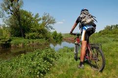 Ciclista in mountain-bike accanto ad un bello fiume Immagini Stock Libere da Diritti
