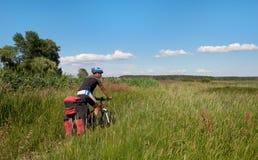 Ciclista in mountain-bike accanto ad un bello fiume Immagine Stock Libera da Diritti