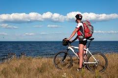 Ciclista in mountain-bike accanto ad un bello fiume Fotografie Stock