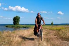 Ciclista in mountain-bike accanto ad un bello fiume Immagini Stock