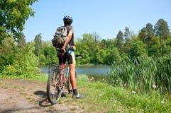 Ciclista in mountain-bike accanto ad un bello lago Fotografie Stock