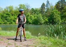 Ciclista in mountain-bike accanto ad un bello lago Immagini Stock