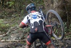 Ciclista in mountain-bike che attraversa fango fotografie stock libere da diritti