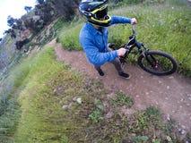 Ciclista in mountain-bike che cammina nel campo di erba del percorso fotografia stock libera da diritti