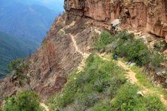 Ciclista in mountain-bike che guida traccia pericolosa giù al canyon di Chicamocha, Colombia immagine stock