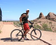 Ciclista in mountain-bike: Ready per le montagne del deserto Immagine Stock