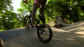Ciclista nel legno Guidando e saltare sopra gli ostacoli Il ragazzo sta guidando nell'aria su Bmx Movimento lento 100 Fps in archivi video