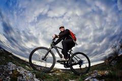 Ciclista nello sportwear nero che guida la bici sulla roccia alla sera contro il bello cielo blu con le nuvole Immagine Stock Libera da Diritti