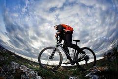 Ciclista nello sportwear nero che guida la bici sulla roccia alla sera contro il bello cielo blu con le nuvole Fotografie Stock