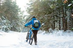 Ciclista no azul que monta o Mountain bike no inverno bonito Forest Extreme Sport e no conceito Biking de Enduro Foto de Stock